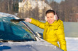 Girl cleaning car from snow