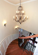 Luxury curved staircase with chandelier and harwood.