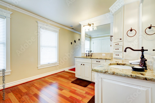 Luxury large white master bathroom with cherry hardwood.