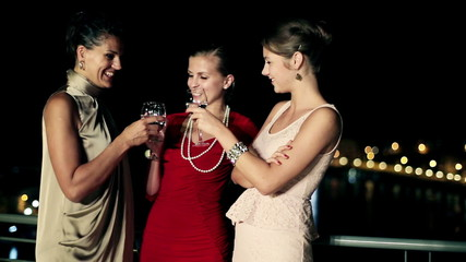 Three female friends enjoying night party on the terrace, crane