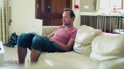 Man sitting on sofa and working on laptop computer