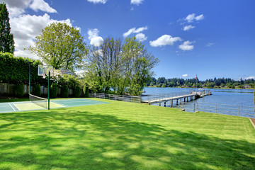 Tennis court with lake and bright green grass.