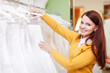 pretty young bride choosing wedding dress