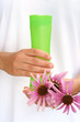 Hands of young woman holding cosmetics bottle and coneflowers