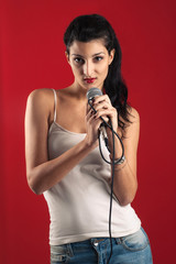 Beautiful girl singing with microphone against red background.