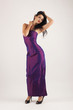 Portrait of sensual brunette caucasian woman with purple dress.