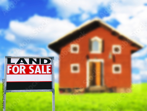 """LAND FOR SALE"" sign against wooden house - Real estate concept"