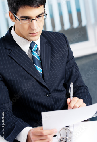 Portrait of reading businessman working at office