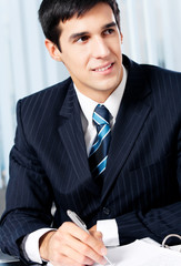 Successful businessman with documents at office