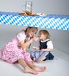 Kinder im Dirndl essen Breze und trinken Apfelschorle