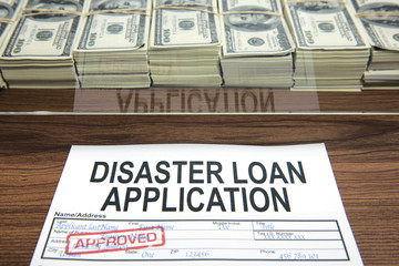 Approved disaster loan application form and dollar bills