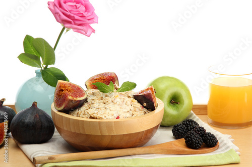 tasty oatmeal with fruits glass of juice, on wooden table