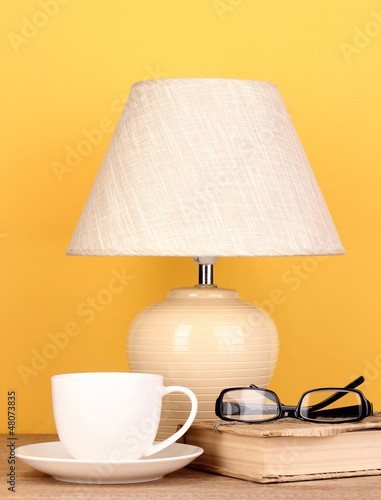 table lamp with cup, book and glasses on yellow background