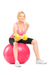 Blond female bodybuilder lifting up a dumbbell seated on a ball