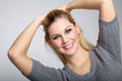 Junge Frau hällt Haare hoch und lacht