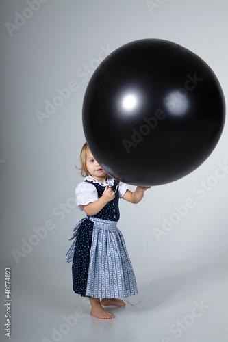 Kleines Mädchen mit riesen Ballon blickt hervor
