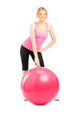 A female athlete posing next to a pilates ball
