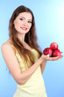 Beautiful woman with apples on blue background