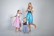 Junge Mutter mit Töchter tanzt im Dirndl und isst Breze