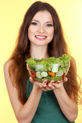 Beautiful woman with vegetable salad on yellow background