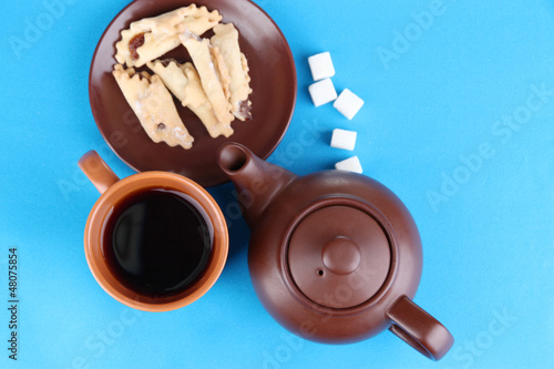 Top view of cup of tea and teapot on blue tablecloths