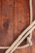 Frame composed of rope on wooden background