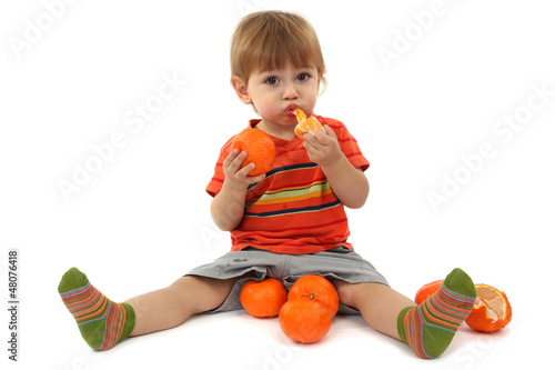 cute little boy eating tangerines, isolated on white