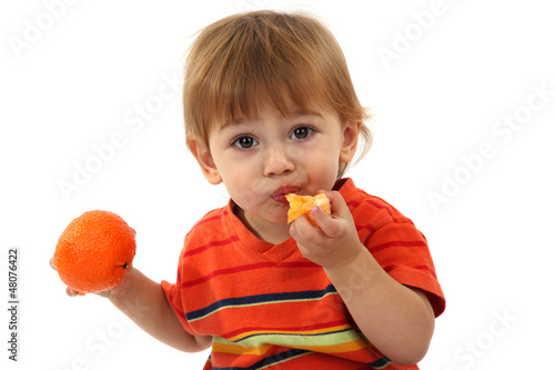 cute little boy eating tangerine, isolated on white
