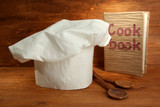 Chef's hat with spoons and cookbook on wooden background