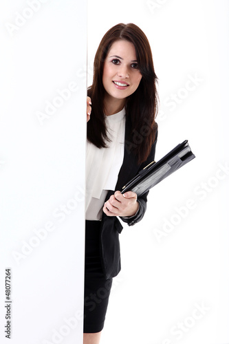 Junge Büro Dame blickt freundlich hinter Wand vor