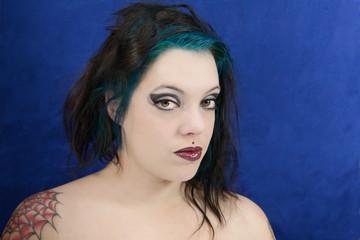 jolie brunette aux mèches bleues piercing tatouage et smoky eyes