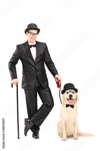 Magician with bow tie holding cane and dog