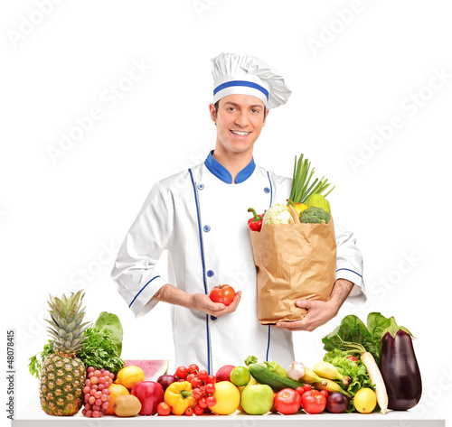 Chef holding a tomato and bag behind a table full of fruits and