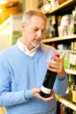 Man holding a glass of wine in a supermarket