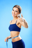 Woman in fitness wear with tape, over blue