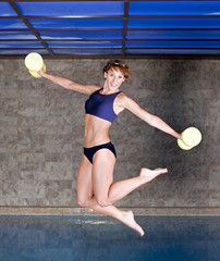 picture of jumping girl with water gear near the swimming pool