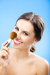 Woman with cosmetics brush, on blue