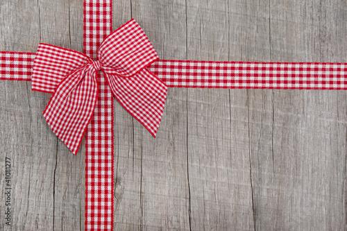 Holztafel mit roter Schleife
