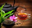 Arrangement aus Teekanne, Teeglas grünem Tee und Orchidee