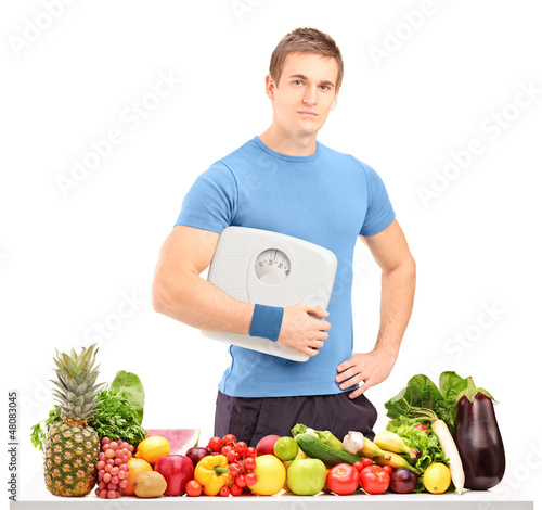 Male athlete holding a weight scale behind a table full of food