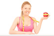 Smiling female holding an apple wrapped with measuring tape