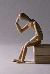 Wooden Modelling Mannequin Sitting and Thinking
