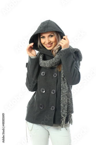 Blonde girl wearing a short gray coat with a long scarf