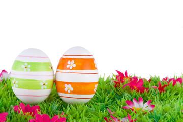 bemalte bunte Eier für Ostern auf Wiese mit Blüten