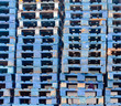 Piled blue wooden euro pallets background pattern