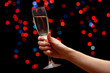 woman hand with glass of champagne, on garland background.