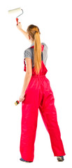 Young woman in red overalls with painting tools