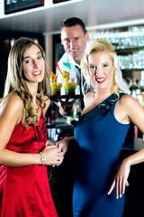 Frauen und Barkeeper in Club oder einer Bar