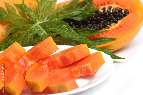 Ripe papaya and slices with seeds and green leaf isolated on a w