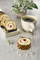 Pastel, brazo de fresa con taza de café.